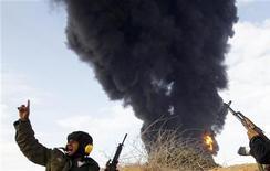 <p>Повстанцы сражаются на дороге между Рас-Лануфом и Бин-Джавадом 9 марта 2011 года. Россия ввела запрет на продажу любого оружия Ливии, сообщила администрация российского президента в четверг. REUTERS/Goran Tomasevic</p>