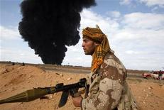 <p>Повстанец, учавствующий в столкновении с войсками Муаммара Каддафи близ порта Рас-Лануф, 9 марта 2011 года. Верные лидеру Ливии Муаммару Каддафи войска нанесли новые удары по занятому мятежниками нефтяному порту Рас-Лануф на востоке страны и остановили продвижение повстанческих сил на запад. REUTERS/Asmaa Waguih</p>
