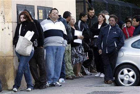People wait in line to enter a government job center in Madrid, October 4, 2010. REUTERS/Andrea Comas
