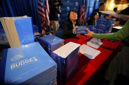 Office of Management and Budget (OMB) employees distribute President Obama's FY2012 budget proposal to members of the press during an event at the Government Printing Office (GPO) in Washington February 14, 2011. REUTERS/Molly Riley