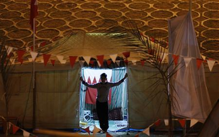 An anti-government protester looks out from his tent at Pearl Square in Manama, March 10, 2011. REUTERS/Hamad I Mohammed