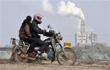 Locals ride a motorcycle past a chemical factory on the suburb of Yingtan, Jiangxi province March 7, 2011. REUTERS/Stringer