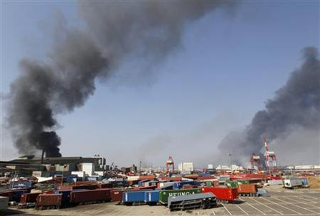 Smoke and scattered containers are seen at a devastated factory area after an earthquake and tsunami in Sendai, northern Japan, March 13, 2011. REUTERS/Kim Kyung-Hoon