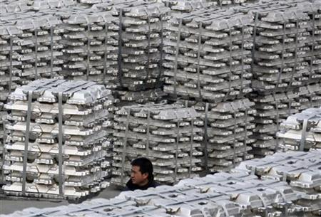 A worker walks among piles of aluminium ingots at a storage of aluminium plant in Yuncheng, Shanxi province January 7, 2010. REUTERS/Stringer