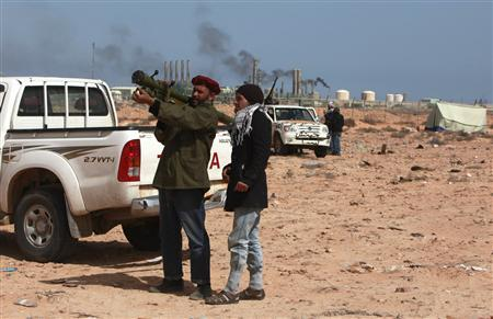 An anti-Gaddafi rebel teaches another about rocket-propelled grenades near the oil facility in Ras Lanuf, March 10, 2011. REUTERS/Asmaa Waguih