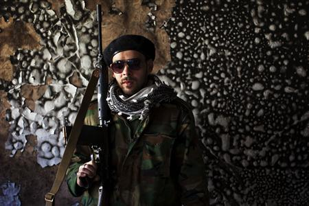 Hesham, 23, an agriculture student who has joined the weeks-old Libyan rebellion, poses for a portrait in a burned out building of a military base in the rebel headquarters of Benghazi, March 14, 2011. REUTERS/Finbarr O'Reilly
