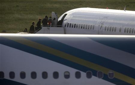 British nationals board an Astraeus Airlines 757 Boeing aircraft waiting to depart to London's Gatwick Airport after being evacuated from Libya at Malta International Airport, outside Valletta February 24, 2011. REUTERS/Darrin Zammit Lupi
