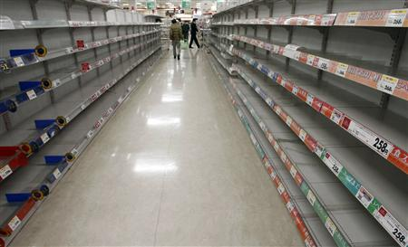 People shop for food from almost empty shelves at a big-box supermarket in Tokyo March 16, 2011. REUTERS/Issei Kato