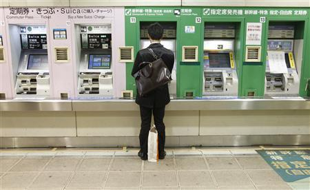 A man buys a bullet train ticket at a station in Tokyo March 16, 2011. REUTERS/Issei Kato