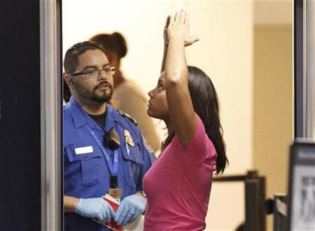 A TSA screener scans a passenger at Fort Lauderdale-Hollywood International Airport in Fort Lauderdale, November 23, 2010. REUTERS/Joe Skipper