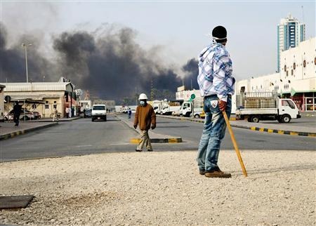 An anti-government protester stands holding a stick as Gulf Cooperation Council (GCC) forces move in to evacuate Pearl Square in Manama March 16, 2011. REUTERS/James Lawler Duggan