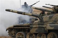 <p>Ливийские солдаты подъезжают на танках к Адждабии 16 марта 2011 года. Войска многолетнего лидера Ливии Муаммара Каддафи продолжают вести бои с силами повстанцев на дороге, ведущей к оплоту мятежников Бенгази, а США все выше оценивают вероятность авиаударов по правительственной армии. REUTERS/Ahmed Jadallah</p>
