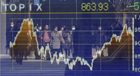 Pedestrians are reflected in a screen displaying the stock index prices in Tokyo March 14, 2011. REUTERS/Issei Kato