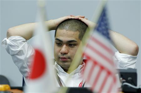 A foreign exchange dealer reacts as he works at a trading room of a foreign exchange trading company in Tokyo, March 18, 2011. REUTERS/Jo Yong-Hak