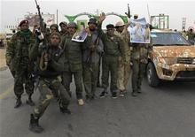 <p>Солдаты армии Муаммара Каддафи около западных ворот города Аждабия 16 марта 2011 года. Ливия решила прекратить все военные действия, согласившись подчиниться резолюции Организации объединенных наций о немедленном прекращении огня, заявил министр иностранных дел Ливии Муса Куса. REUTERS/Ahmed Jadallah</p>