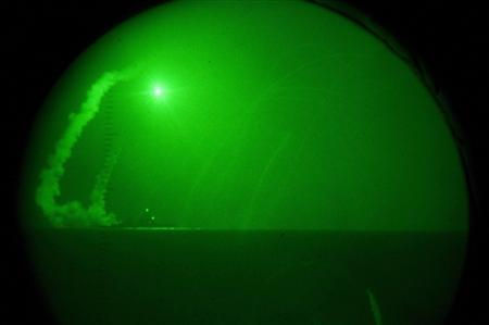 Seen through night-vision lenses aboard amphibious transport dock USS Ponce (LPD 15), guided missile destroyer USS Barry (DDG 52) fires Tomahawk cruise missiles in support of Operation Odyssey Dawn in the Mediterranean Sea on March 19, 2011 and released to Reuters on Saturday. REUTERS/Nathanael Miller/U.S. Navy photo/Handout