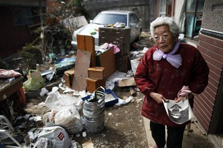 Teru Suzuki, 86, holds a picture of her son Kazuo who died in a tsunami in 1960 as she tells her story at her home which was destroyed by the recent tsunami in Ofunato March 20, 2011. ''It could only be destiny'', says Suzuki, after surviving not only the massive earthquake and tsunami in northeastern Japan last week but two other big earthquakes in her lifetime. REUTERS/Damir Sagolj