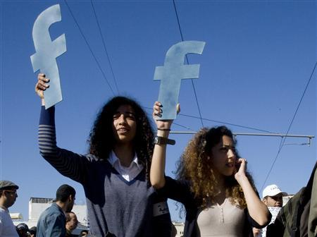 Protesters hold ''f''s in recognition of social network site Facebook's role in the North African revolts, during a protest in Rabat March 20, 2011. REUTERS/Adam Tanner