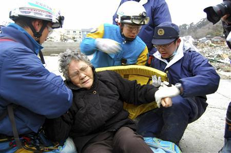 80-year-old Sumi Abe (C) is helped by emergency workers after being rescued from under the rubble in Ishinomaki City, Miyagi Prefecture, northern Japan, in this picture taken by Nikkei Shimbun on March 20 , 2011. Sumi and her 16-year-old grandson Jin Abe were found alive on Sunday under the rubble in Ishinomaki in northeast Japan, nine days after the earthquake. REUTERS/Asahi Shimbun