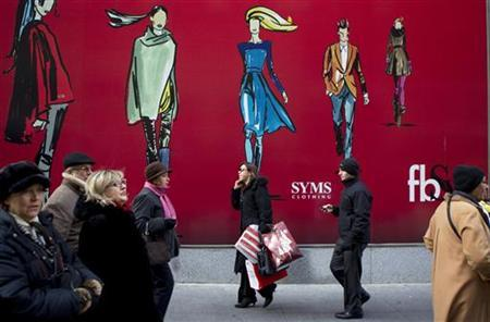 A woman walks with shopping bags past an advertisement on 5th Avenue in New York December 22, 2010. REUTERS/Lucas Jackson