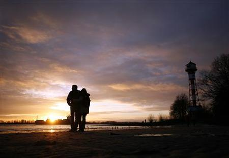 A couple watches the sunset next to the lighthouse of Wittenberge on the Elbe river near Hamburg January 13, 2008. REUTERS/Christian Charisius