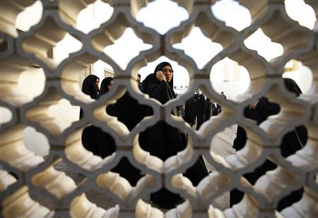 A family member of Bahiya al-Aradi, a woman who was killed during riots, stands next to the door of a mosque to welcome other family members and friends, during her funeral in Manama March 22, 2011. REUTERS/Hamad I Mohammed