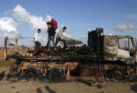People stand atop a destroyed truck loaded with weapons belonging to forces loyal to Libyan leader Muammar Gaddafi, after a coalition air strike, along a road between Benghazi and Ajdabiyah March 21, 2011. REUTERS/Suhaib Salem