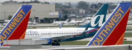An AirTran airlines jet (C) taxis past two Southwest jets sitting at their gates at Midway International airport in Chicago September 27, 2010. REUTERS/Frank Polich