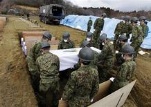 <p>Members of the Japan Ground Self Defense Force carry the coffin of a victim of the tsunami at a temporary mass grave site in Higashi Matsushima, northern Japan March 23, 2011. REUTERS/Yuriko Nakao</p>
