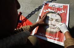 <p>Оппозиционер разрисовывает газету с изображением экс-президента Египта Хосни Мубарака в Каире, 12 февраля 2011 года. Специальный комитет, созданный в Египте для расследования случаев насилия во время антиправительственных демонстраций, выдвинул в адрес экс-президента страны Хосни Мубарака и бывшего министра внутренних дел обвинения в умышленном убийстве протестующих, сообщила в среду газета Al Ahram. REUTERS/Amr Abdallah Dalsh</p>
