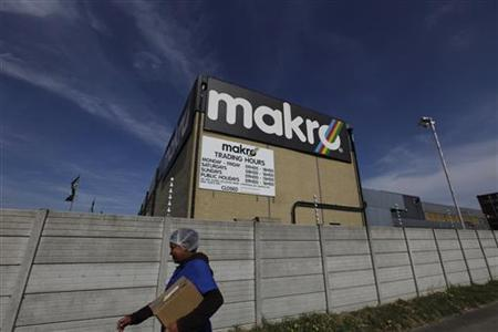 A woman walks past a Makro branch of the South African retailer Massmart in Cape Town, September 30, 2010. REUTERS/Mike Hutchings