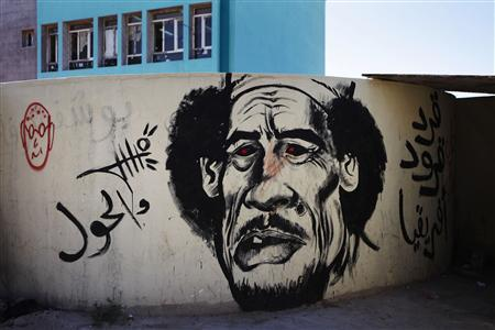 Revolutionary graffiti caricaturing Muammar Gaddafi adorns a wall in Benghazi March 23, 2011. REUTERS/Finbarr O'Reilly