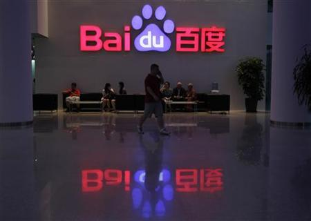 A employee uses his mobile phone as he walks past the company logo of Baidu at its headquarters in Beijing, August 5, 2010. REUTERS/Barry Huang