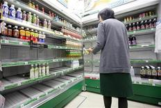 <p>Женщина стоит перед полупустыми полками с питьевой водой в магазине в Токио, 24 марта 2011 года. Объявление водопроводной воды в Токио опасной для грудных детей из-за радиации, распространяющейся с аварийной АЭС в Фукусиме, привело к дефициту бутилированной воды в магазинах столицы, а также увеличению числа стран, отказывающихся от импорта японских продуктов. REUTERS/Aly Song</p>