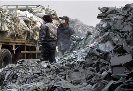 Workers wearing face masks load discarded piles of sacks onto a truck at a rare earth smelting plant located on the outskirts of the city of Baotou in China's Inner Mongolia Autonomous Region October 31, 2010. REUTERS/David Gray
