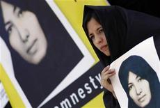 <p>An activist of the human rights organization Amnesty International holds a picture of Iranian citizen Sakineh Mohammadi Ashtiani during a demonstration in front of Iran's Embassy in Buenos Aires, November 5, 2010. REUTERS/Marcos Brindicci</p>