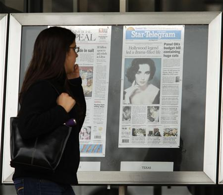 A pedestrian walks by today's newspaper front pages with the late Elizabeth Taylor obituary on display in front of the Newseum in Washington, March 24, 2011. REUTERS/Hyungwon Kang