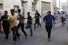 <p>Bahraini men flee during a protest as riot police enter their village of Dai, east of Manama, March 24, 2011. REUTERS/Hamad I Mohammed</p>