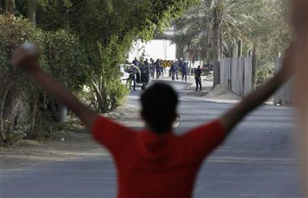 An anti-government protester gestures to riot police in the mainly Shi'ite village of Diraz, west of Manama, March 25, 2011.REUTERS/Hamad I Mohammed