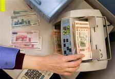 """<p>Кассир пересчитывает белорусские рубли в банке в Минске 29 января 2010 года. Ажиотажный спрос на доллары и евро в Белоруссии, подстегнутый недоверием к национальной валюте и подъемом зарплат бюджетникам накануне президентских выборов, истощил валютную казну и грозит девальвировать """"$500 в месяц"""", которые Александр Лукашенко обещал народу перед переизбранием. REUTERS/Vasily Fedosenko</p>"""
