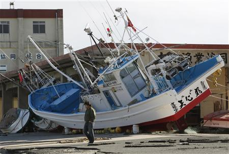 A man walks past a boat that was swept ashore after the March 11 earthquake and tsunami, at Otsu port in Kitaibaraki, Ibaraki prefecture, March 27, 2011. REUTERS/Issei Kato