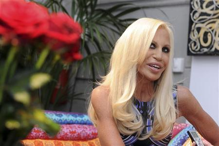 Italian designer Donatella Versace poses near creations, part of the Versace home collection, during Milan Design Week April 14, 2010. REUTERS/Paolo Bona