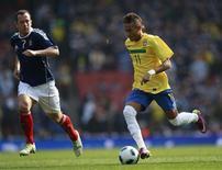 <p>O atacante brasileiro Neymar (direita) e o escocês Charlie Adam (esquerda) em amistoso Brasil x Escócia no Emirates Stadium, em Londres. Durante o jogo, um turista alemão admitiu ter jogado uma banana em campo. 27/03/2011 REUTERS/ Eddie Keogh</p>