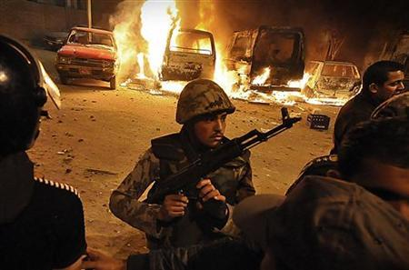 A soldier guards the area as protesters burn police vehicles outside the police security headquarters after clashes with Egyptians in Alexandria, north of Cairo, March 4, 2011. REUTERS/Stringer