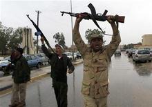 <p>Солдаты армии Муаммара Каддафи под Триполи, 30 марта 2011 года. Ливийские повстанцы продолжают отступать под натиском войск лидера страны Муаммара Каддафи на фоне появившейся информации о том, что президент США Барак Обама подписал секретный приказ о тайном оказании помощи мятежникам. REUTERS/Ahmed Jadallah</p>
