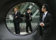 <p>A businessman (R) glances at other men through a work of outdoor art in Tokyo April 2, 2007. REUTERS/Toru Hanai</p>