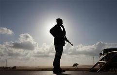 <p>Повстанец стоит на КПП между городами Адждабия и Бенгази, 31 марта 2011 года. Известие о бегстве главы МИД в Лондон обрадовало ливийских мятежников, расценивших его как доказательство постепенного развала режима Муаммара Каддафи. REUTERS/Andrew Winning</p>