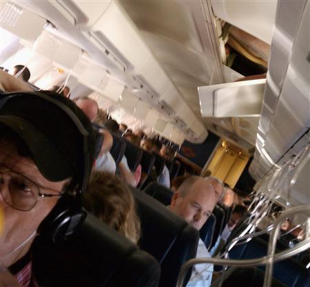 A hole is seen above passengers onboard a Southwest Airlines flight from Phoenix to Sacramento, California April 1, 2011. The Southwest Airlines plane, with a gaping hole in the fuselage, made an emergency landing at a military base in Arizona on Friday after a sudden drop in cabin pressure, airline officials said. REUTERS/Shawna MalviniRedden via Twitter