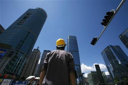 A construction worker crosses a street at a business district in Shenzhen, China's southern Guangdong province July 16, 2009.REUTERS/Bobby Yip