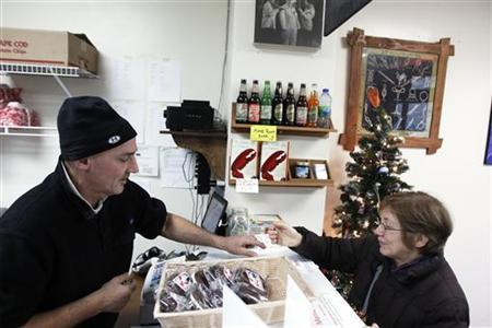Small-business owner Ralph Gorham (L) sells lobster by the pound to a customer at his shop ''Redhook Lobster Pound'' in New York December 16, 2010. REUTERS/Lucas Jackson